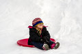 Laughing girl with hat over her eyes a little on a red saucer sled laughs as falls as she reaches the bottom of the hill Royalty Free Stock Photo
