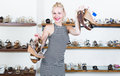 Laughing girl holding many pair of shoes Royalty Free Stock Photo