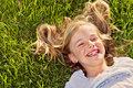Laughing girl lying in grass Stock Photo