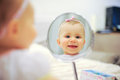 Laughing girl in mirror reflection of round Stock Photography