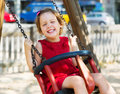 Laughing girl in red on chain swing playground Stock Photography