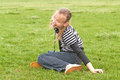 Laughing girl sits on a green grass Royalty Free Stock Photo