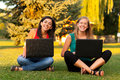 Laughing girls outdoors with laptop Stock Photos