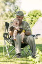 Laughing grandfather and grandson smiling holding his in a chair outside Stock Image