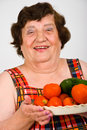 Laughing grandma holding tomatoes Stock Photos
