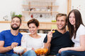 Laughing group of friends watching television frontal view a diverse young sitting on a sofa and eating snacks Stock Image
