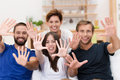 Laughing group of young people with upheld hands playful holding up their palms towards the camera and outspread fingers focus to Stock Image