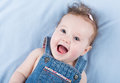 Laughing happy baby girl wearing a jeans dress little Royalty Free Stock Photos