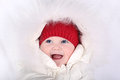 Laughing happy baby in white snow suit and red knitted hat Royalty Free Stock Photo
