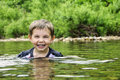Laughing and happy little boy in the water playing with his head shoulders above Royalty Free Stock Image