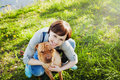 Laughing happy young woman in denim overalls hugging her red cute dog Shar Pei in the green grass in sunny day, true friends forev Royalty Free Stock Photo