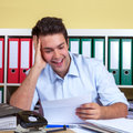 Laughing hispanic guy reading a message at office in blue shirt an feeling happy about the good newswriting his Royalty Free Stock Image