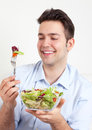 Laughing hispanic guy on a sofa loves green salad in blue shirt fresh and healthy Royalty Free Stock Images
