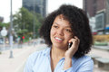 Laughing hispanic woman in the city talking at phone Royalty Free Stock Photo