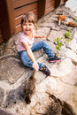 Laughing kid girl feeding ducks with hands Royalty Free Stock Photo
