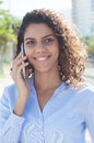 Laughing latin woman with blue blouse at phone in the city Royalty Free Stock Photo