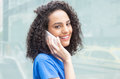 Laughing latin woman with curly hair at phone in city Royalty Free Stock Photo