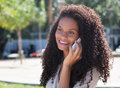Laughing latin woman with long curly hair at phone Royalty Free Stock Photo