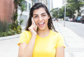 Laughing latin woman with yellow shirt at phone in city Royalty Free Stock Photo