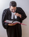Laughing at the law man in canadian lawyer toga holding a book of it Stock Photos