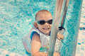 Laughing little boy climbing out of a pool Royalty Free Stock Photo