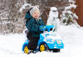 Laughing little boy drives toy car on snow Royalty Free Stock Photo