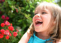 Laughing little girl near red flowers Stock Images