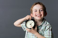 Laughing little kid with missing tooth holding clock for time Royalty Free Stock Photo