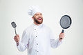 Laughing male chef cook holding spoon and pan