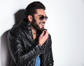 Laughing man in leather jacket pulling his beard side view of a and sunglasses Royalty Free Stock Photos