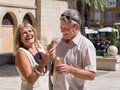 Laughing mature senior couple eating ice cream having fun together while he try to steal her cone on a hot summer day as they Stock Photos