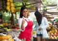 Laughing mexican saleswoman showing thumb on a farmers market Royalty Free Stock Photo