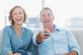 Laughing middle aged couple sitting on the couch watching tv at home in living room Royalty Free Stock Images