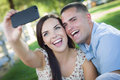 Laughing mixed race couple taking self portrait in park happy with a smart phone the Stock Images