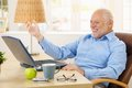 Laughing old man using laptop computer at home looking at screen gesturing Stock Image