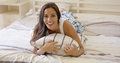 Laughing playful young woman relaxing in bed Royalty Free Stock Photo