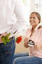 Laughing pregnant woman with ultrasound baby picture in hand getting red rose from man Royalty Free Stock Image