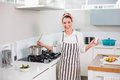 Laughing pretty woman with apron cooking in bright kitchen Royalty Free Stock Images
