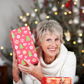 Laughing senior lady with a christmas gift holding it up to her face in front of tree sparkling bokeh of lights Stock Images