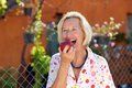Laughing senior woman eating a red apple opening her mouth wide to take bite as she stands in the garden in the sunshine Royalty Free Stock Image