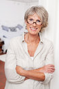 Laughing senior woman with folded arms attractive wearing glasses standing Royalty Free Stock Photography