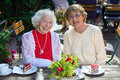 Laughing senior women seated with cake pair of cute friendly slices of on wooden table in outdoor cafe Stock Photo