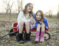 Laughing sisters and best friends two young preteen girls sit in a wagon together Royalty Free Stock Photos