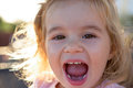Laughing spontaneous little toddler girl spontaneously while looking at you with showing her teeth Royalty Free Stock Photos