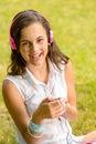 Laughing teenage girl listen music sitting grass listening to on summer Stock Photo