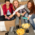 Laughing teenage girls playing with video game with consoles Royalty Free Stock Photos