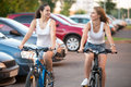 Laughing teenage models compete on bicycles