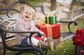 Laughing toddler child sitting on bench with christmas gifts outside happy young Royalty Free Stock Photography