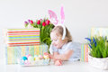 Laughing toddler girl in blue dress and bunny ears happy with curly hair wearing a playing with easter presents eggs colorful Royalty Free Stock Photos