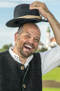 Laughing traditional bavarian man portrait of a in clothes with monestary andechs in bavaria germany Royalty Free Stock Images